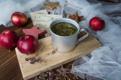 Tisane dans une tasse en métal et des pommes rouges Image stock
