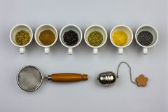 Tisane ingredients with strainers. Tisane ingredients - fennel seeds, cinnamon, juniper seeds, mallow, ginger, poppy seeds Royalty Free Stock Images