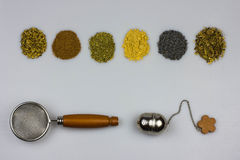 Tisane ingredients with strainers. Fennel seeds, cinnamon, mallow, ginger, poppy seeds, lemon balm Stock Photos