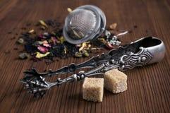 Tisane, tamis de thé, cubes en sucre et pinces Photographie stock