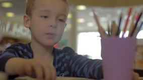 Am Tisch zeichnet das Sitzen eines kleinen Jungen und mit farbigen Bleistiften stock video
