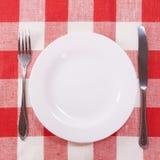 Tischbesteck auf checkered Tischdecke Stockfotografie