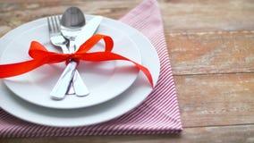 Tischbesteck gebunden mit rotem Band auf Platte stock footage
