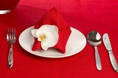Tischbesteck mit Blumen auf einer roten Tischdecke Lizenzfreie Stockfotografie