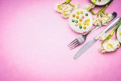 Tischbesteck mit schönen Narzissenblumen und -kuchen auf rosa Hintergrund, Draufsicht, Platz für Text Ostern-Lebensmittel Stockbild