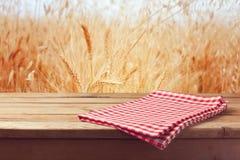 Tischdecke auf Holztisch über Weizenfeld Stockfotografie