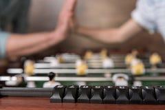 Tischfußball und Hände, die Hoch fünf auf Hintergrund geben Lizenzfreie Stockbilder