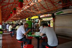 Tischgäste essen Tischen an den im Freien Maxwell Food Center Singapore Stockbild