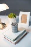 Tischlampe, Bilderrahmen und Bücher auf Tabelle Lizenzfreie Stockfotografie