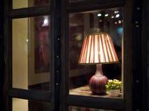 Tischlampe hinter Fenster Lizenzfreies Stockbild