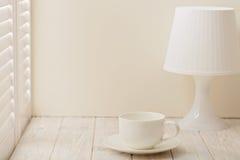 Tischlampe mit Schatten und Schale auf einem hellen hölzernen Hintergrund Stockbild