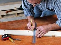 Tischler bei der Arbeit über das Holz Stockbild