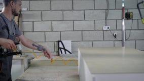 Tischler benutzt Möbelhefter für das Reparieren der Rückplatte zur Spanplattengarderobe in einer Werkstatt stock video