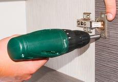 Tischler bringt die Garderobe an und schraubt eine Schraube, Möbeltürscharnier, unter Verwendung des drahtlosen Schraubenziehers Lizenzfreies Stockfoto