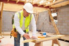 Tischler-Cutting House Roof-Unterstützungen auf Baustelle Stockfotografie