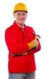 Tischler, der den Tischlerhammer betrachtet Kamera und lächelnden Isolator hält Lizenzfreies Stockfoto