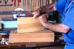 Tischler, der ein Stück Holz in der Werkstatt seines Hauses planiert lizenzfreie stockbilder
