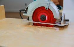 Tischler, der einen Küchenschrank mit der Kreissäge während der Hauserneuerung schneidet lizenzfreies stockfoto