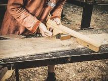Tischler in der mittelalterlichen Baumwollkleidung, die mit dem Flugzeug mit einem Holz arbeitet Mann gießt manuell Sägemehl vom  stockfotos