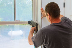 Tischler, der Nagelgewehr zu den Formteilen auf Fenstern verwendet, Gestaltungsordnung, stockbilder
