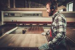 Tischler, der seins Arbeit in der Zimmereiwerkstatt tut Lizenzfreie Stockfotos