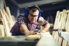 Tischler, die hölzerne Planke mit einer Kreissäge schneiden lizenzfreies stockfoto