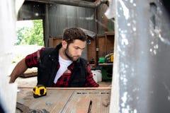 Tischler, hölzerne Arbeitskraftarbeit, die Bauholzprodukt misst, bohrt und macht lizenzfreies stockbild