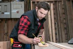 Tischler, hölzerne Arbeitskraftarbeit, die Bauholzprodukt misst, bohrt und macht lizenzfreie stockbilder