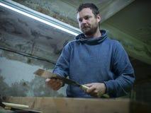 Tischler mit einem Bart, der einen Holzbalken mit einer Handsäge sägt ein Tischler, der ein Stück Holz sägt stockbild