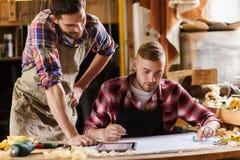 Tischler mit Machthaber und Plan an der Werkstatt Lizenzfreies Stockfoto