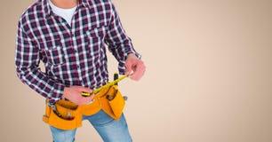 Tischler mit messendem Band gegen Sahnehintergrund Stockbild