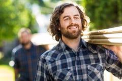 Tischler-Smiling While Carrying-Planken mit Lizenzfreie Stockbilder