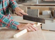 Tischler Using Small Saw, zum des Holzes zu schneiden Stockfotos
