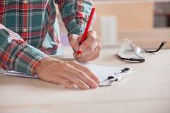 Tischler-Writing Notes On-Klemmbrett bei Tisch Lizenzfreie Stockfotografie