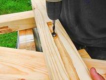 Tischlerfunktion, Bohrgerät und hölzerner Holzbauweiseholzarbeitwerktischhintergrund in der Zimmerei Stockfotos