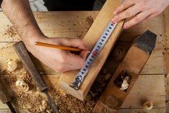 Tischlerfunktion, -hammer, -meter und -schraubenzieher auf Bauhintergrund Stockfotografie