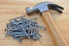 Tischlerhammer und Stapel von Nägeln Lizenzfreie Stockfotos