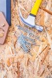 Tischlerhammerhandsaw und -nägel auf Sperrholz Lizenzfreies Stockfoto