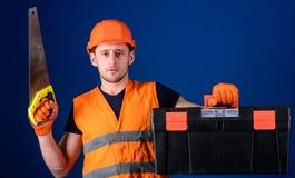 Tischlerkonzept Mann im Sturzhelm, Schutzhelm trägt Werkzeugkasten und hält Handsaw, blauen Hintergrund Arbeitskraft, Reparaturha Lizenzfreies Stockfoto