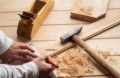 Tischlerwerkzeuge, Hammer, Meter, Nägel, Schnitzel und Lizenzfreie Stockbilder