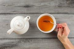 Tischplatteansicht - Frauenhand, die Löffel, rührenden Tee im Weiß hält lizenzfreie stockbilder