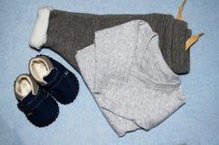 TischplatteansichtdekorationsBabyschuhe und Kleidung, Körper sut und Hosen Flache Lage stockfotografie
