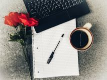 Tischplattenansicht der Laptop-Computers, des Tasse Kaffees, des Notizbuches und des Pen Withs rote Rose On The Side, Innenminist lizenzfreies stockfoto