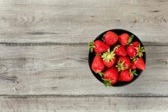 Tischplattenansicht, kleine schwarze keramische Schüssel mit Erdbeeren, grauer hölzerner Schreibtisch darunter Raum für Text auf  lizenzfreie stockfotografie