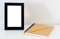 Tischplattenrahmen und Notizbuch Stockfotografie