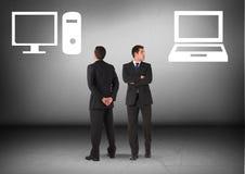 Tischrechner oder Laptop mit dem Geschäftsmann, der in den entgegengesetzten Richtungen schaut Lizenzfreie Stockfotos