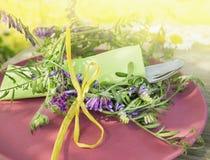 Tischschmuck mit Wickenblumen und grünem Stoff auf roter Platte Stockbilder