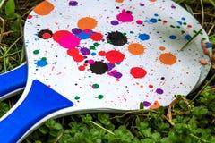 Tischtennisschläger/-paddel mit den farbigen Flecken, liegend auf dem Gras Stockfotografie