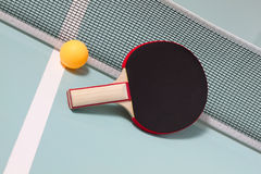 Tischtennisschläger und -kugel Stockfotos