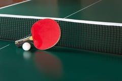Tischtennisschl?ger und ein Ball auf einer gr?nen Tabelle Tischtennisnetz stockbilder